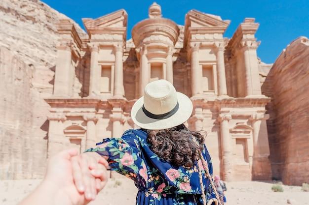 Mulher jovem, em, vestido colorido, e, chapéu, segurando, mão homem, e, guiando, ele, para, a, mosteiro