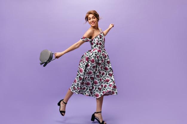 Mulher jovem em vestido floral segura bolsa e pula. jovem bonita atraente com penteado elegante em pose de roupa de verão.