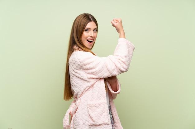 Mulher jovem, em, vestindo, vestido, sobre, verde, parede, fazer, forte, gesto