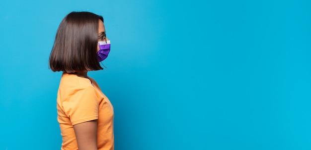 Mulher jovem em vista de perfil olhando para copiar o espaço à frente, pensando, imaginando ou sonhando acordada