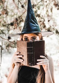 Mulher jovem, em, wizard, chapéu, encerramento, boca, com, livro