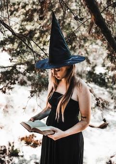 Mulher jovem, em, wizard, chapéu, livro leitura, em, madeiras