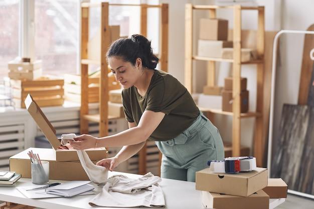 Mulher jovem embalando uma blusa nova em uma caixa no local de trabalho, trabalhando em uma loja virtual