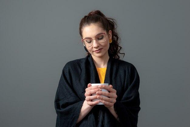 Mulher jovem emocional de cabelos cacheados em uma capa preta segurando um copo branco de bebida quente com as duas mãos