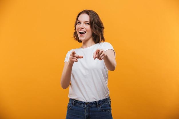 Mulher jovem emocional feliz apontando para você.
