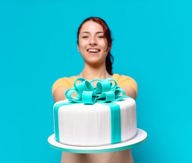 Mulher jovem empregada de padaria com um bolo de aniversário