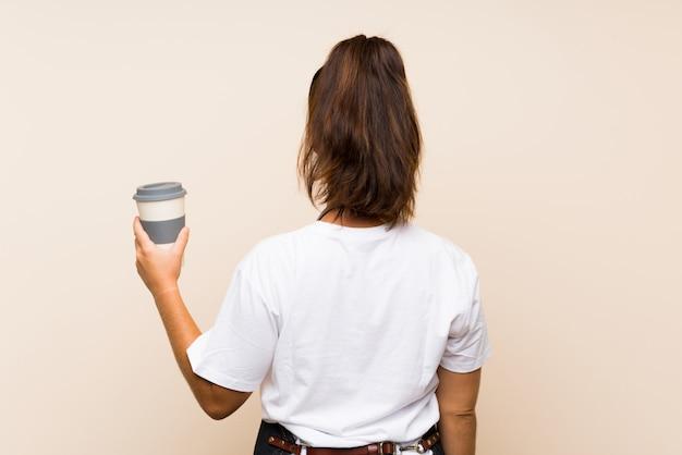 Mulher jovem empregado segurando um café para viagem em posição traseira