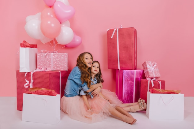Mulher jovem encaracolada animada numa jaqueta retrô, abraçando sua filha descalça, rodeada de caixas de presentes coloridas. menina charmosa de cabelos compridos sentada no chão com a mãe depois da festa de aniversário