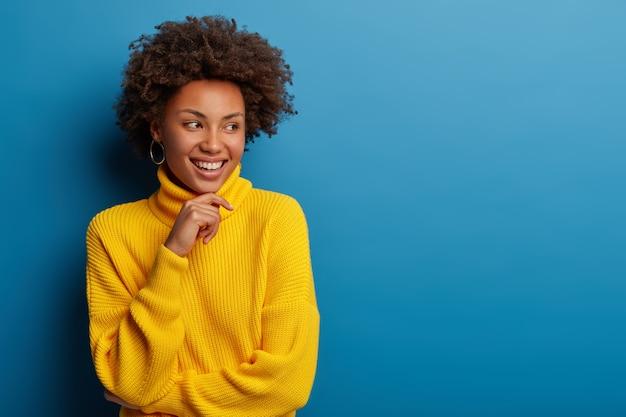 Mulher jovem encaracolada positiva vestida com um suéter amarelo confortável, segura o queixo, olha de lado com uma expressão sonhadora, tem uma ideia interessante em mente, isolada sobre fundo azul.