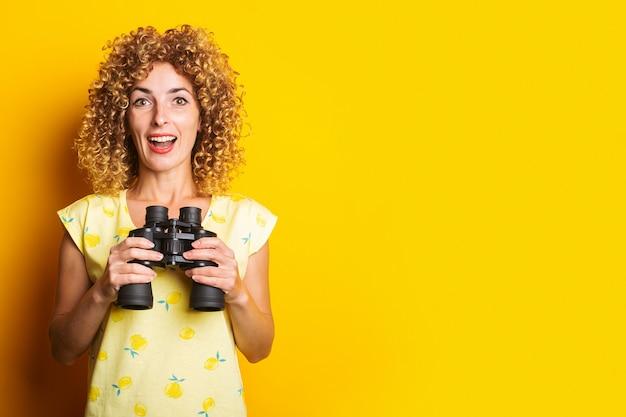 Mulher jovem encaracolada surpresa e alegre com binóculos em uma superfície amarela