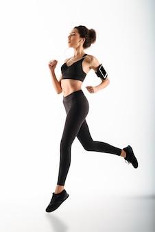 Mulher jovem encaracolado morena fitness correndo e ouvindo música