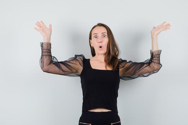 Mulher jovem encolhendo os ombros em uma blusa preta e calça preta e parecendo chocada, vista frontal.