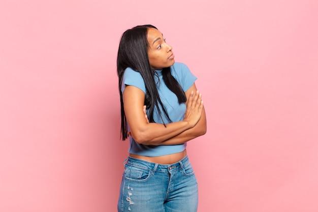 Mulher jovem encolhendo os ombros, sentindo-se confusa e incerta, duvidando com os braços cruzados e olhar perplexo