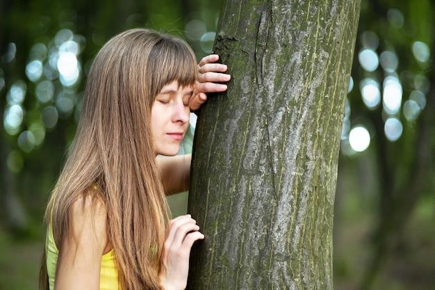 Mulher jovem encostada no tronco de uma árvore na floresta de verão