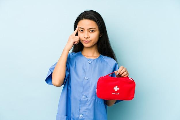 Mulher jovem enfermeira chinesa isolada em um azul, mostrando um gesto de decepção com o dedo indicador.