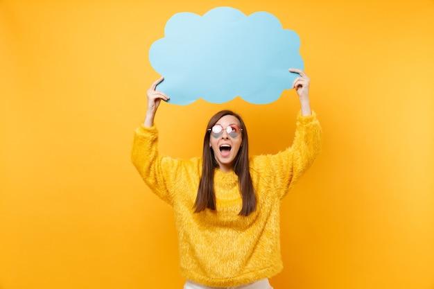 Mulher jovem engraçada animada em óculos de coração segurando vazio azul em branco say nuvem, balão de fala isolado em fundo amarelo brilhante. emoções sinceras de pessoas, conceito de estilo de vida. área de publicidade.