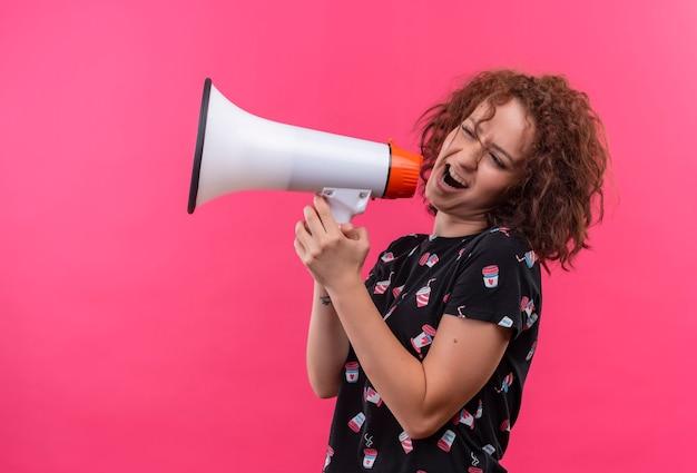 Mulher jovem engraçada com cabelo curto e cacheado gritando para o megafone