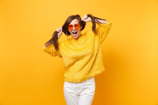 Mulher jovem engraçada com suéter de pele, calça branca e óculos coração laranja segurando o cabelo como um rabo de cavalo isolado no fundo amarelo brilhante. emoções sinceras de pessoas, conceito de estilo de vida. área de publicidade.