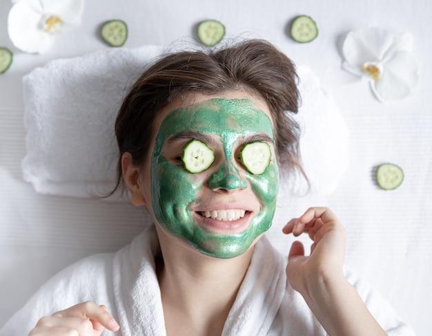Mulher jovem engraçada com uma máscara cosmética no rosto e pepinos nos olhos.
