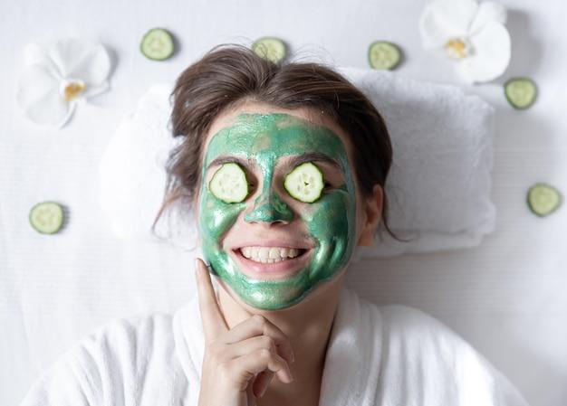 Mulher jovem engraçada com uma máscara cosmética no rosto e pepinos nos olhos