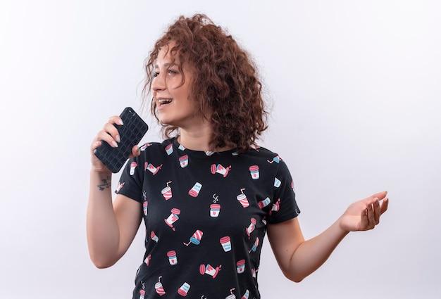 Mulher jovem engraçada e alegre com cabelo curto e encaracolado segurando um smartphone usando como microfone cantando uma música