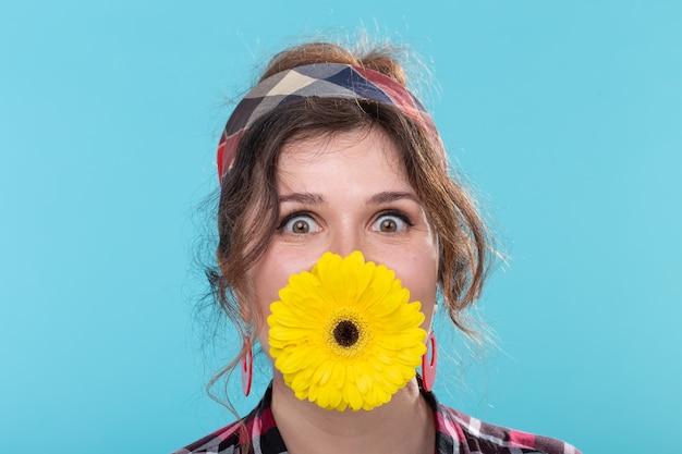 Mulher jovem engraçada e positiva em imagem retrô segurando uma flor gerbera amarela brilhante entre os dentes
