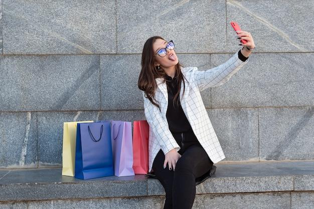 Mulher jovem engraçada fazendo selfie na rua com suas sacolas de compras