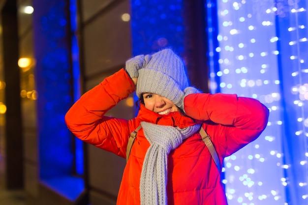 Mulher jovem engraçada feliz com roupas de inverno, noite, cidade, luzes, iluminação, natal