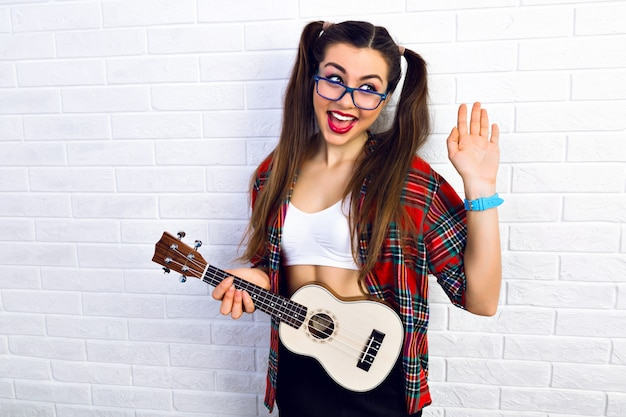 Mulher jovem engraçada hippie se divertindo e tocando violão ukulele, cantando e dançando.