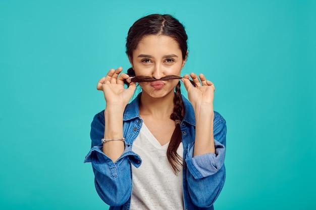Mulher jovem engraçada mostra um bigode, parede azul, emoção positiva. expressão facial, pessoa do sexo feminino olhando para a câmera no estúdio, conceito emocional, sentimentos