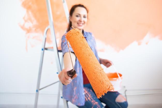 Mulher jovem engraçada pintando a parede interior com rolo de pintura na casa nova