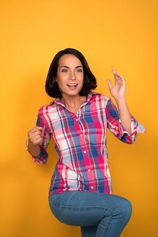 Mulher jovem engraçada se alegra com a vitória de sorte. conceito de fortuna. morena caucasiana de riso vestindo jeans. isolado em fundo amarelo.