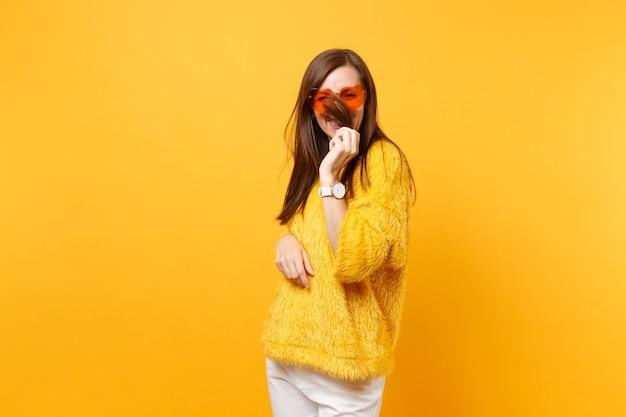 Mulher jovem engraçada sorridente no suéter de pele e óculos coração laranja segurando, cobrindo o rosto com o cabelo isolado no fundo amarelo brilhante. emoções sinceras de pessoas, conceito de estilo de vida. área de publicidade.