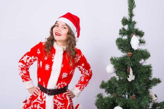 Mulher jovem engraçada usando fantasia de papai noel perto da árvore de natal