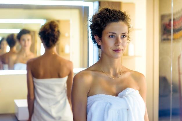 Mulher jovem enrolada em uma toalha branca limpa se refletindo várias vezes em espelhos paralelos em uma perspectiva decrescente em um banheiro