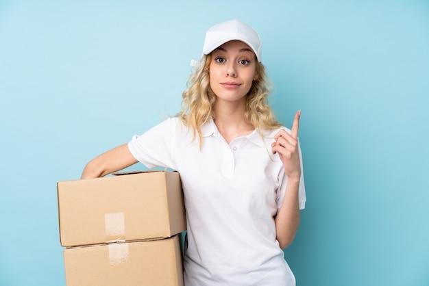 Mulher jovem entrega isolada na parede azul apontando com o dedo indicador uma ótima idéia