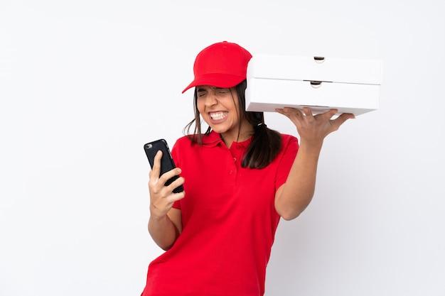 Mulher jovem entrega pizza sobre parede branca isolada com telefone em posição de vitória