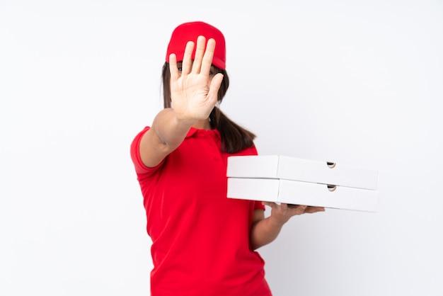 Mulher jovem entrega pizza sobre parede branca isolada, fazendo o gesto de tempo