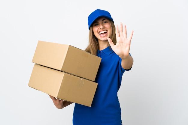 Mulher jovem entrega sobre parede branca isolada, contando cinco com os dedos