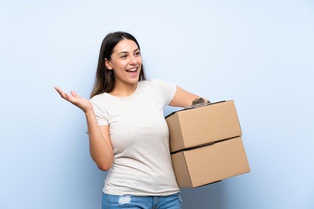 Mulher jovem entrega sobre parede de tijolo azul com expressão facial de surpresa