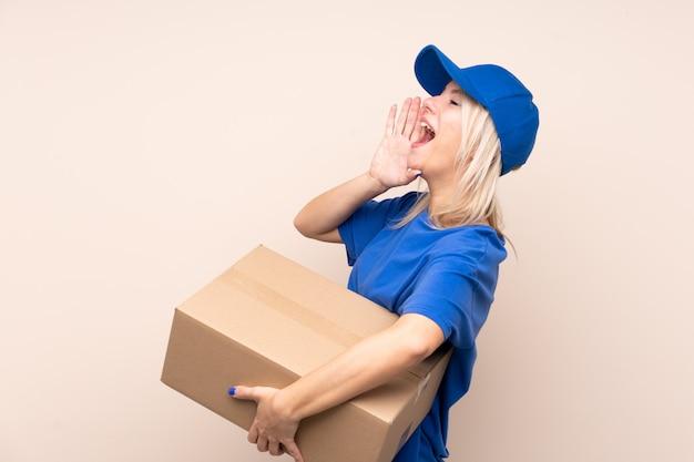 Mulher jovem entrega sobre parede isolada, gritando com a boca aberta