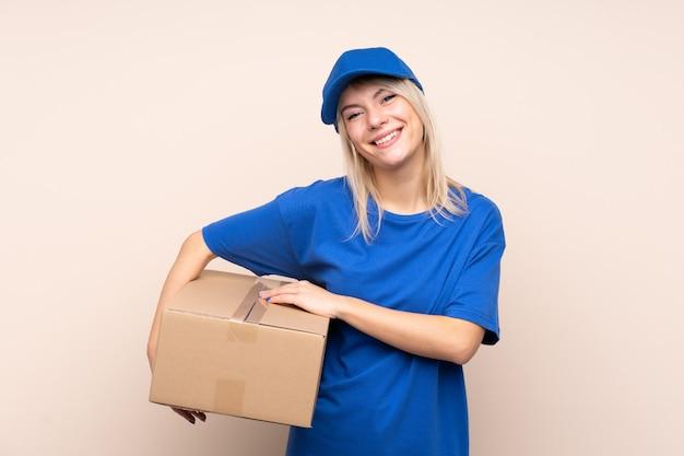 Mulher jovem entrega sobre parede isolada rindo
