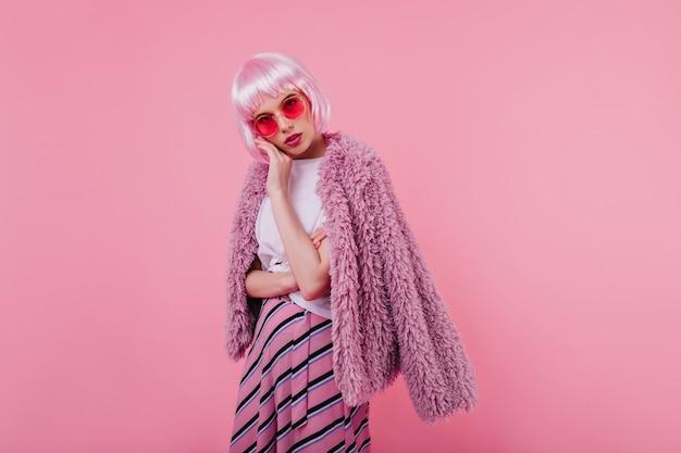 Mulher jovem entusiasmada em peruca e elegantes roupas cor de rosa posando. garota séria e glamourosa em peruke em pé na parede iluminada