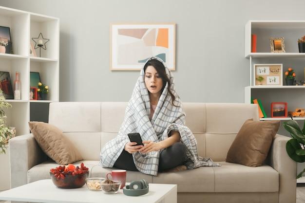 Mulher jovem envolvida em um manto segurando e olhando para o telefone, sentada no sofá atrás da mesa de centro na sala de estar