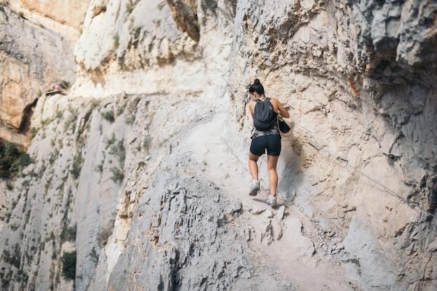 Mulher jovem escalando caminhada em uma montanha estreita