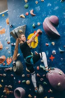 Mulher jovem, escalando, um, alto, indoor, parede artificial, escalada