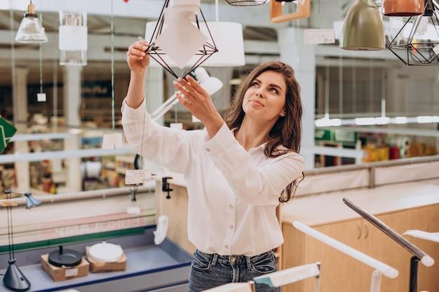 Mulher jovem escolhendo lustre no centro de construção