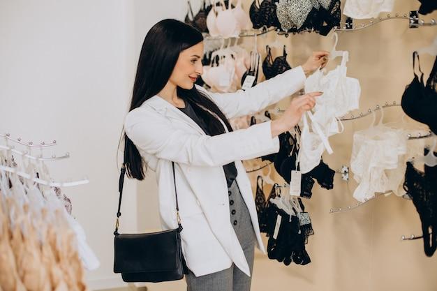 Mulher jovem escolhendo roupas íntimas em shopping