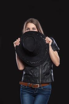 Mulher jovem escondida atrás de um chapéu de cowboy preto