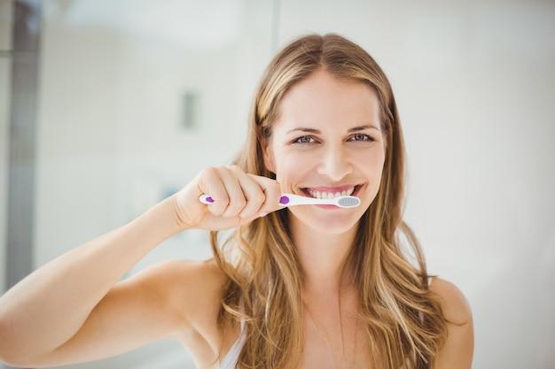 Mulher jovem, escovar dentes